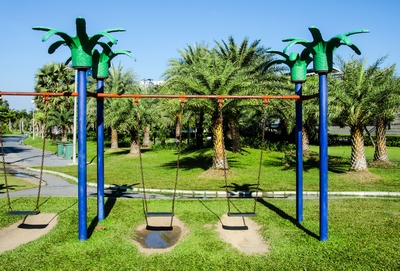natural grass and dirt below playground swings